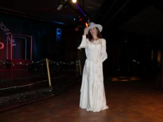 In Wedding Dress and White Hat on stage