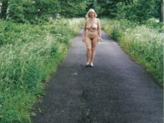 Mature nude walks in English country lane at one with nature