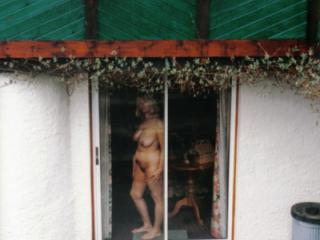 Nude mature photographed by watcher using telephoto lens
